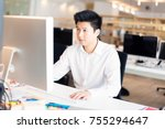 Small photo of a young asian office worker is sitting at his desk. he could be a designer, programmer or a businessman.