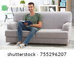 young man reading book on sofa... | Shutterstock . vector #755296207