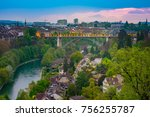 Small photo of Scenic View of Bern Capital City with Buildings and Beautiful Bridge, Cloudy Sky at Sunset Time, View of the Old City of Bern from The Stone Bridge, over Aare river, Switzerland.