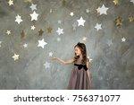 little girl in gray dress is... | Shutterstock . vector #756371077