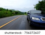 Small photo of Blue sedan car parking side of asphalt road against hill with fog.
