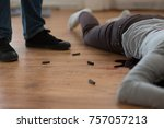 Small photo of murder, kill and people concept - criminal or murderer with bleeding dead woman body lying on floor and bullet sleeves at crime scene
