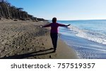 one woman walking on the beach | Shutterstock . vector #757519357