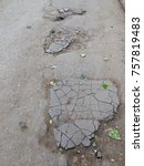 Small photo of Bad roads, broken asphalt. Ruined and badly repaired asphalt close up. Pits and potholes on the road.
