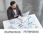 Small photo of Portrait of busy male office worker makes voice call, discuss documents with partner, compare result, try to predict wastes for next month. Head executive officer holds balance sheet and mobile phone