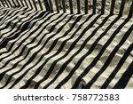 Small photo of Pattern of shadows cast by sand fence along oceanside beach, for themes of conservation, vacation, transience or alternation