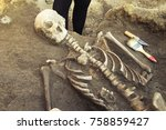 Small photo of Archaeological excavations and finds (bones of a skeleton in a human burial), working tool, ruler, knife, brush, a detail of ancient research, prehistory.