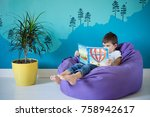 Small photo of Caucasian boy reading an ABC book in his room with a beautiful turquoise mountain mural.