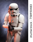 Small photo of SAN BENEDETTO DEL TRONTO, ITALY. NOVEMBER 11, 2017. Studio portrait of stormtrooper costume replica, with blaster E-11 gun. He is a fictional character of Star Wars saga. Red reflexes