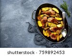 Small photo of Chicken legs baked with potato in a skillet over dark grey slate,stone or concrete background.Top view.