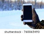 smartphone in hand in the woods. | Shutterstock . vector #760065493