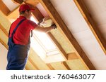Small photo of house attic insulation - construction worker installing rock wool in mansard wall