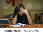 Small photo of Fail the exam. Tired and bored young female student girl sits at the school desk and holds her head with her hand feel an ailment headache. Education concept.