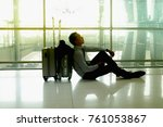 Small photo of Young businessman sat at the airport at sunset. Disappointed by delayed flight delay.