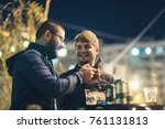Small photo of Two friends are in the city at night, they drink beer and bet online from their phone. Bet on football matches or check the latest news from smartphone for dating applications