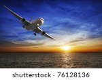 Night flight. Jet aircraft over the sea at dusk. - stock photo