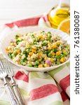 Small photo of Salad with bulgur, green peas, corn, onion and greens on white rustic wooden table. Tabbouleh. Selective focus.