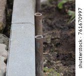 Small photo of Tools for installing concrete curb stone and string with metal stakes to level at sidewalk construction site. Selective focus.