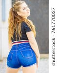 Small photo of Back view of young teenage woman wearing short blue jeans denim shorts enjoying summer weather