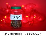 Small photo of Red background with christmas lights and glass jar with coins (moneybox) collected or saved for 2018 New year. Concept of money save for realization of plans and dreams