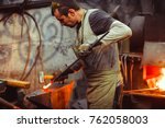 blacksmith working on an anvil | Shutterstock . vector #762058003