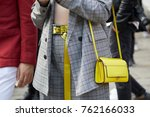 Small photo of MILAN - SEPTEMBER 22: Woman with yellow leather bag and gray checkered suit before Versace fashion show, Milan Fashion Week street style on September 22, 2017 in Milan.