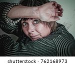 Small photo of Fearful women of middle age hopelessly closed her face with her hands.