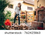 girl raking up autumn leaves in ... | Shutterstock . vector #762425863