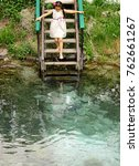 Small photo of Beautiful girl in beautiful dress goes down to the spring. Bathing in the spring. Bathing in spring water. Kids games on the water.