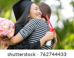Small photo of Educational theme.Beautiful woman graduating huging her family with holding her diploma and smiling in an academic gown