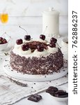 Small photo of Black forest cake, Schwarzwald pie, dark chocolate and cherry dessert on a white wooden cutting board.