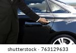 Small photo of Driver hand opening car door