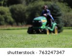 Small photo of Estonia, Tartu, 26.08.2017. A male worker using a ride on lawn mower John Deere X540 in a park. Blurred