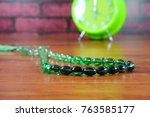 Small photo of String of beads is used for Muslims in their tasbih (in English is the repetitive utterances glorification of Allah). Conceptual isolated and selective focused photo with the brick background