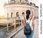 Small photo of Young tourist woman portrait in Berlin. Bode Museum in the background. Lifestyle concept.