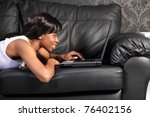Beautiful smiling young african american woman lying on black leather sofa at home, surfing on the internet with her laptop computer. - stock photo