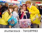 Small photo of Birmingham, UK - November 18, 2017: Cosplayer at Birmingham MCM Comic Con dressed as characters from Love Live! with 'ita bags'. Ita bags are bags covered with items featuring a favourite character.