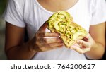woman hand show eating avocado... | Shutterstock . vector #764200627