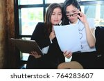 Small photo of Two businesswoman working together about documents, partner discuss plan or idea and opinion meeting, Asian bussiness are discussing their working on a wood table beside window at coffee shop