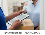 Small photo of Delivery man using card reader to accept payment for package delivery
