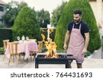 young man preparing barbecue in ... | Shutterstock . vector #764431693