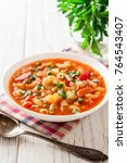 Small photo of Italian minestrone soup on white wooden background. Selective focus.