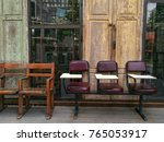 Small photo of Two styles of chairs are line abreast on wooden plank in front of yellow and green closed doors and windows
