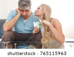 Small photo of Blonde gold digger wife asking 100 Euro from sad husband, indoors