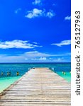 Small photo of wooden batten bridge juts out into the expanse of the sea Dominican Republic