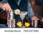 Small photo of Bartender garnishing drink, pouring fresh lime margarita in fancy glass at restaurant