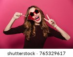 Small photo of Image of young beautiful lady wearing glasses standing isolated over pink background. Looking camera eating candy make peace gesture.
