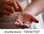 bride keeps earrings with green ...   Shutterstock . vector #765367537