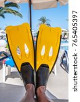 Small photo of Flippers on the feet of a vacationer lying on a sun lounger by the pool