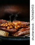 Small photo of Close-up of delicious hot baked beans and smoky crispy pork bacon on fried toasted bread, shot against a creative, rustic background with generous accommodation for copy space.